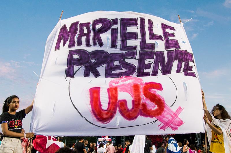 """A Assembleia das Democracias, sediada ontem (15) no estádio do Pituaçu, zona norte de Salvador, parte da programação do Fórum Social Mundial, começou de verdade quanto, aos gritos de """"olê olê olê olá, Lula, Lula"""", o furioso público irrompeu através das cercas de metal que os distanciavam do palco, invadindo a área vip onde a grande maiorias das cadeiras de plástico, cuidadosamente dispostas em fila, quedavam quase que completamente desocupadas."""