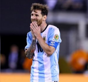 Messi com a mão no rosto lamentando uma derrota