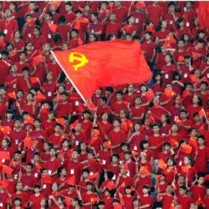 Multidão de jovens vestidos de vermelho balançam uma grande bandeira da China