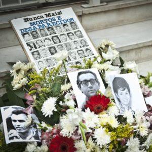 Uma coroa de flores e fotos de pessoas desaparecidas no período da ditadura de 45-85