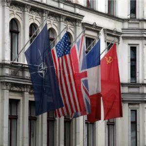 Bandeiras da OTAN, EUA, Reino Unido, Rússia e China em frente a fachada histórica