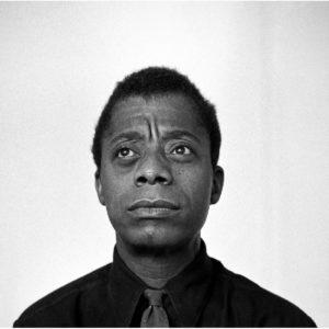 Foto em preto e branco de James Baldwin sobre fundo branco. Ele olha alto para o horizonte.