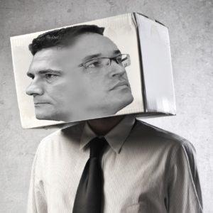 Imagem de torso com cabeça de caixa. Na caixa, aparecem os rostos de Deltan e Moro.