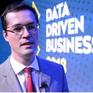 """Imagem de Deltan Dalagnol posando em frente a um banner no qual se lê """"Data Driven Business 2018"""""""