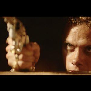 O personagem Lunga aponta uma arma escondido em uma fresta