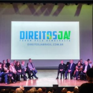 """Palco do TUCA no dia do evento """"Direitos Já"""". Uma projeção com o slogan da campanha ao fundo e diversas lideranças políticas sentadas à frente."""